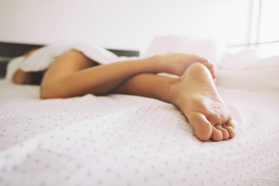woman in bed, feet-first view