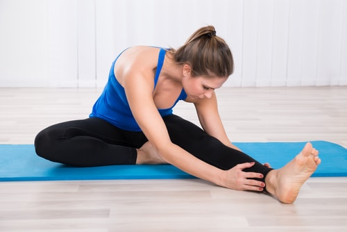 woman doing yoga stretch on blue yoga mat