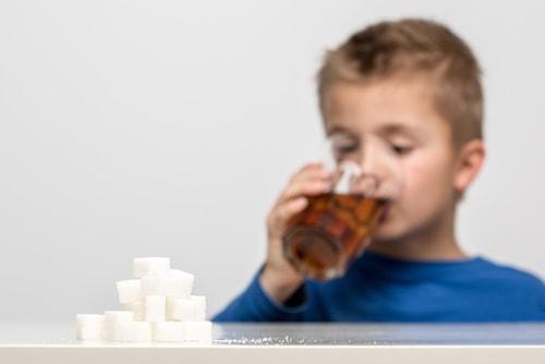 kid drinking sugary drinks dangerous to health