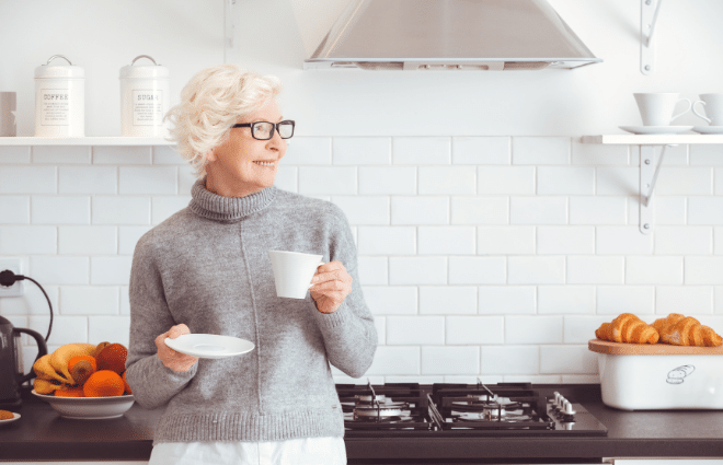 older woman drinking coffee in a kitchen