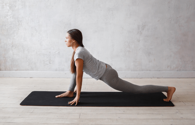 woman doing yoga lunge with hands on mat near feet, back knee down