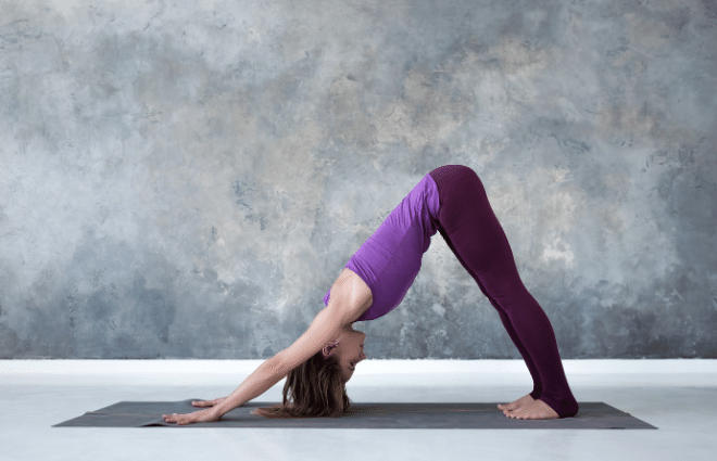woman in purple outfit doing downward dog yoga pose