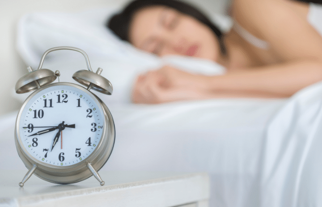 woman sleeping in background, alarm clock in front