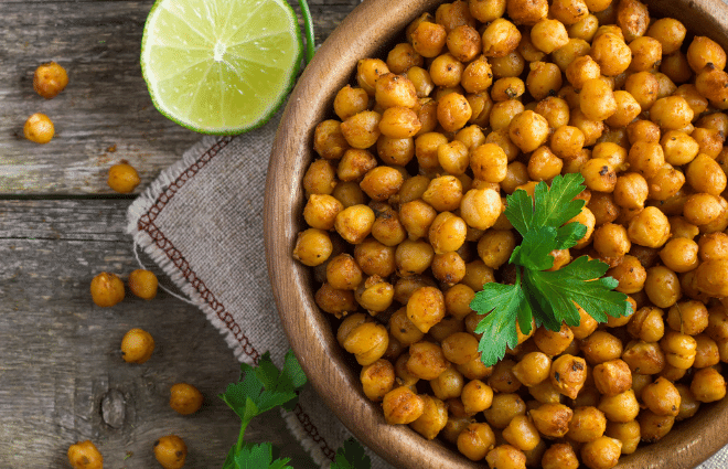 chickpeas in a bowl with a lime and green herbs