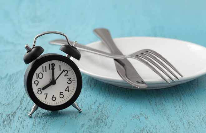 clock and empty plate with knife and fork, intermittent fasting