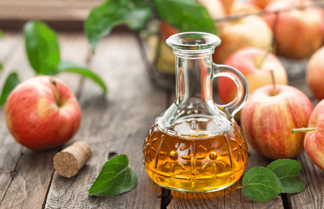 apple cider vinegar in a bottle with fresh apples and leaves