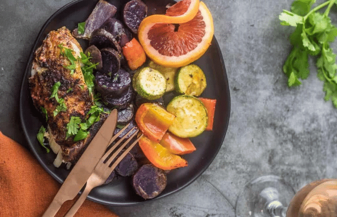 Mexican roasted chicken and veggies on dark plate