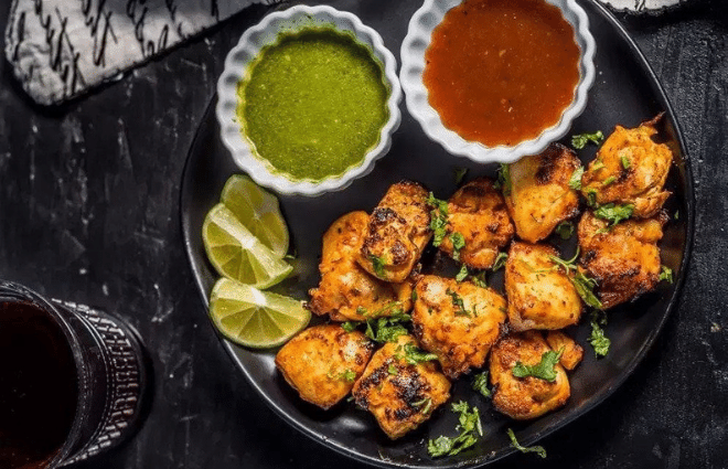 grilled chicken tikka with green and red sauce on the side