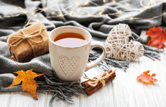 cozy holiday self care scene, tea and fall leaves