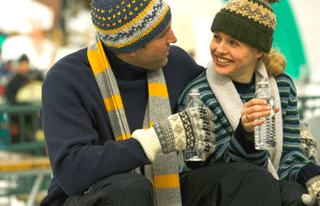 man and woman in winter clothes drinking water