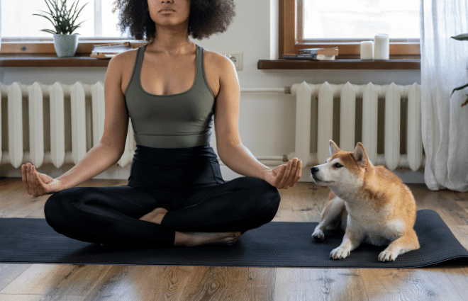 woman meditating at home with her dog